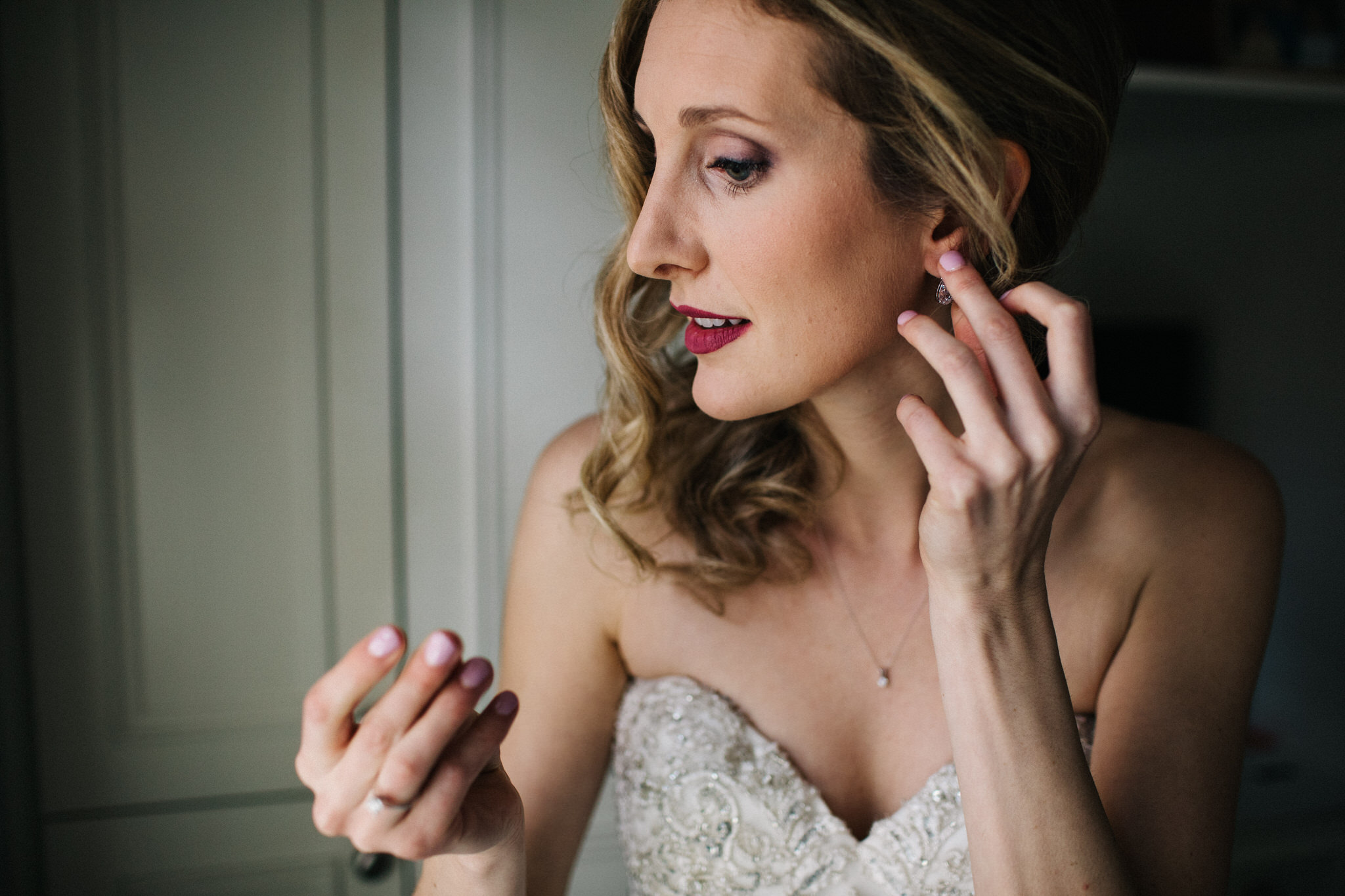 bride putting on earings, bride getting ready, berkeley church wedding, toronto wedding photographer